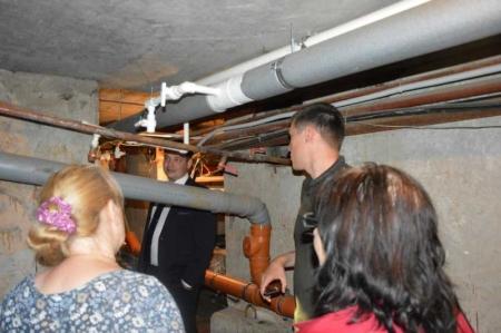 И.о. министра вместе с жильцами оценивает новые трубы в подвале